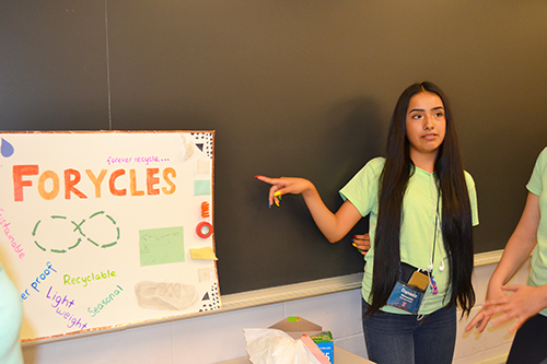 A high school student presents her team's design project at the end-of-the-camp poster session.