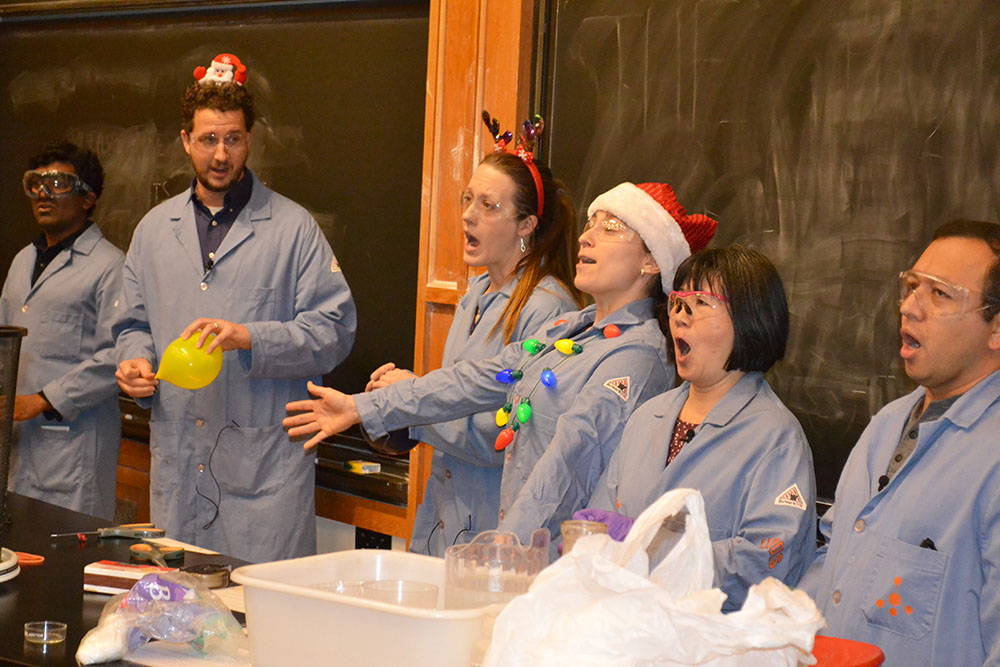 everal of Chemistry's teaching faculty, Mutha Gunasekera, Christian Ray, Elise McCarren, Jordan Axelson, Tina Huang, and José Andino perform the opening number for the 2019 Holiday Magic Show.