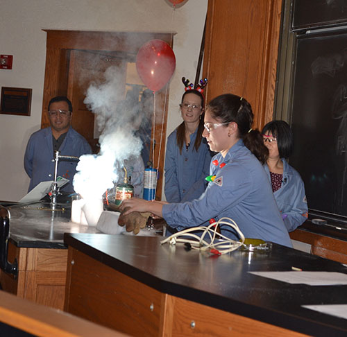 The exothermic chemical reaction in the demo done by Jordan Axelson produces a number of byproducts: heat, light, gas, smoke.