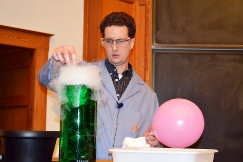 Christian Ray drops dry ice into a beaker  of green liquid to set the ambiance for the show.