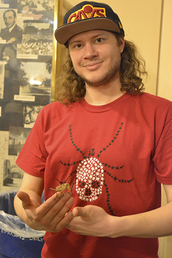 Entomology PhD student and EGSA president Charles Dean holds a grasshopper.