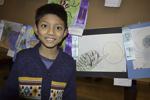 A young visitor proudly poses with the drawing he made as part of the art contest