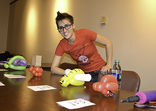 An entomology Ph.D. student helping out at the balloon insects station shows the balloon insects kids could have made for themselves—all of which she designed
