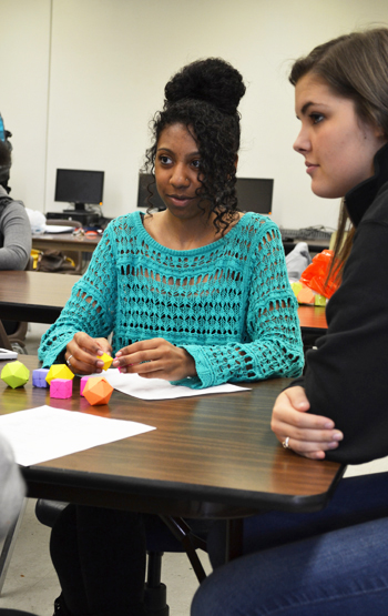 Local high school student uses geometric shapes to conceptualize a math principle during a Tap-In afterschool program at Centennial.