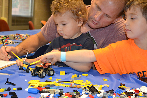 Two brothers build spacecraft during ISD's Lego hands-on activity.