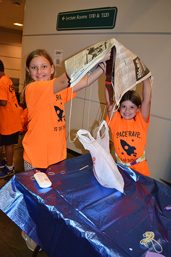 Two young visitors show off the parachute they built for the egg drop activity.