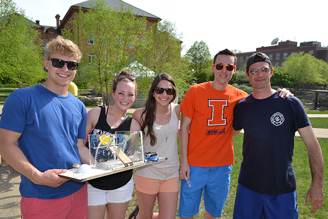 Team of CE370 students show their BLAM design which allowed them to successfully dunk two professors, including Davin Horn (right).