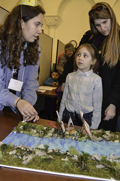 Illinois sophomore Emily Alameda does the Crossing the River acitvity with a local youngster at the Riddle Mania station during the Math Carnival: Gathering for Gardner.