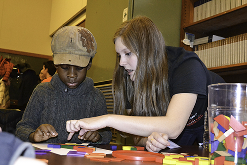 An Illinois math student (right) works on a tile puzzle with a local youngster at the Math Carnival's Tile Emporium station.
