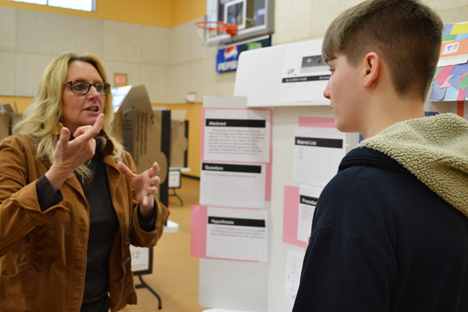 Science Educator and EnLiST Project Coordinator Anita Martin discusses a student's project with him.