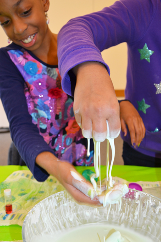 Two NGS students demonstrate the part solid/part liquid properties of oobleck.