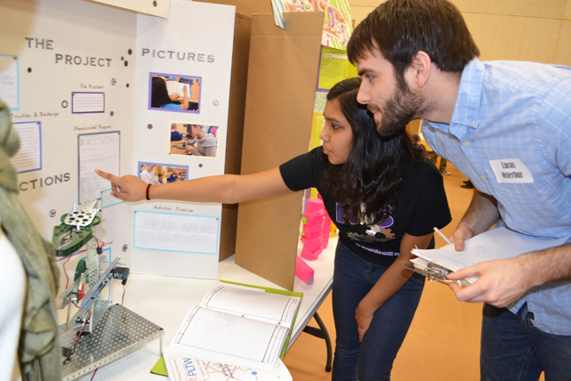 Eighth grader explains the Pick and Place robot she helped design to <em>Illinois'</em> Lucas Osterbur during judging at  Next Generation's Science & Engineering Fair.