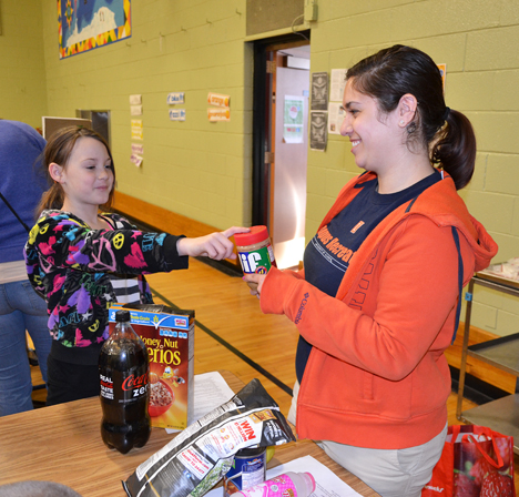 Leila Shinn and a student play a game about nutrition.