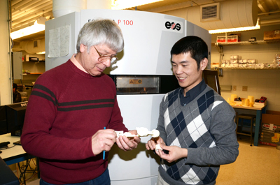 Jim Phillips (left) and Keng Hsu examine a model created in the Ford Manufacturaing Lab