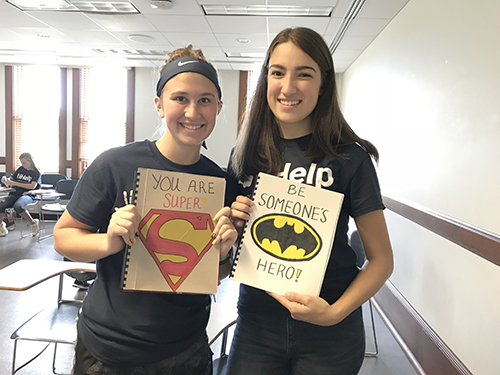 Left to  right: SWE members </strong>Taylor Wills and Dionora Osmani hold notebooks they made  out of one-sided recycled white paper, complete with a cereal box or cardstock cover, which  they decorated themselves, as part of SWE's Project Paplet. (Image courtesy of Berat Gulecyuz.)