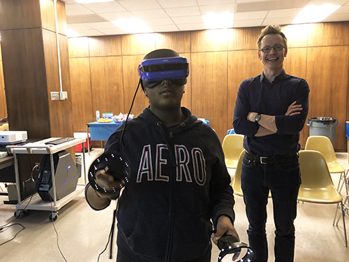 Andre Schleife (right) enjoys exposing a student to virtual reality during a visit to MRL. (Image courtesy of Andre Schleife.)