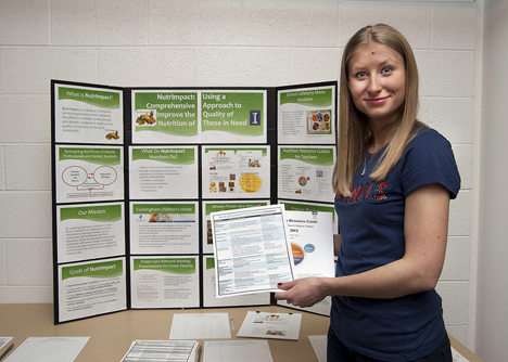Lisa Shkoda presents NutrImpact posters and materials at the 2013 Public Engagement Symposium.