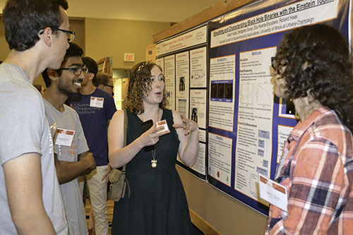 Bridgette Davey cheerfully goes over the results of her team's research with other students.