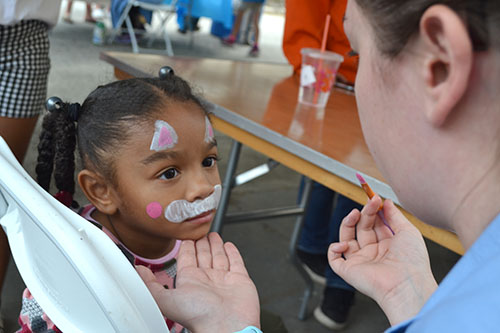 Vet Med student Aiden Tansey paints the face of young visitor.