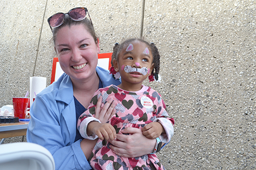 Vet Med student Aiden Tansey and her young friend, face painted as a...bunny?