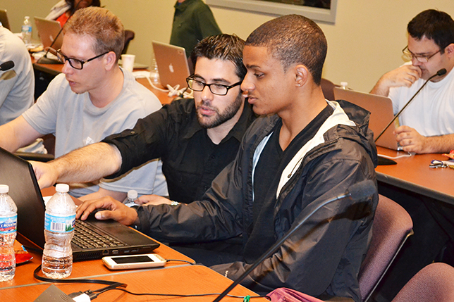 Mobeen Ludin (center) works with a Blue Waters intern during a coding workshop