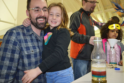 A SWE DADDS participant and her dad have a great time bonding while makeing a rainbow jar.