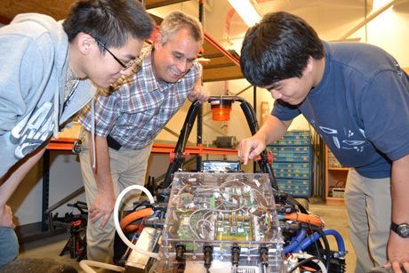Two students and Mike Philpott examine Hybrid's circuitry