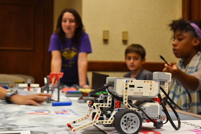 Becca Nothof (left) and a team discuss the success of their robot at the practice competition.