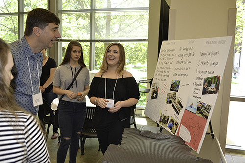 MechSE's Joe Muskin (upper left) looks on as a Centennial student explains about her team's research during the IRISE 2017 Symposium held last spring.