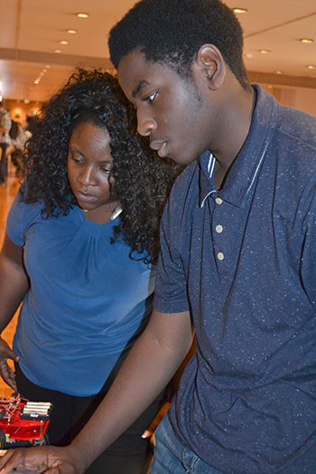 D.J. Jackson (right), Centennial sophomore, walks his mom, Antonia Jackson, through the project's code.