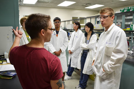 Chieli Moldonado (right) and some of the other campers listen as grad student Derek Varden explains about biofuels.